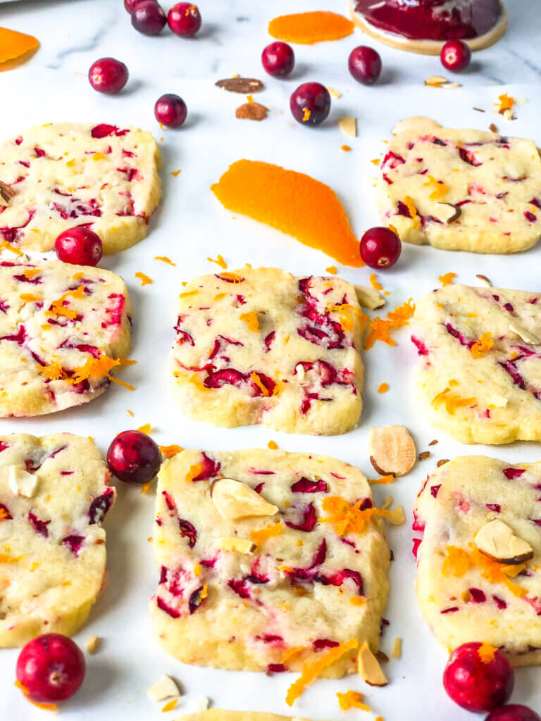 Blog post photo - 45-degree shot showing columns of shortbread cookies, with one missing. Scattered cranberries and orange zest