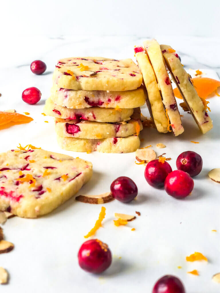 blog photo showing Stack of 4 square Almond Shortbread cookies with orange and cranberries, with 3 more stacked sideways against it and another lying in front with scattered orange zest and cranberries