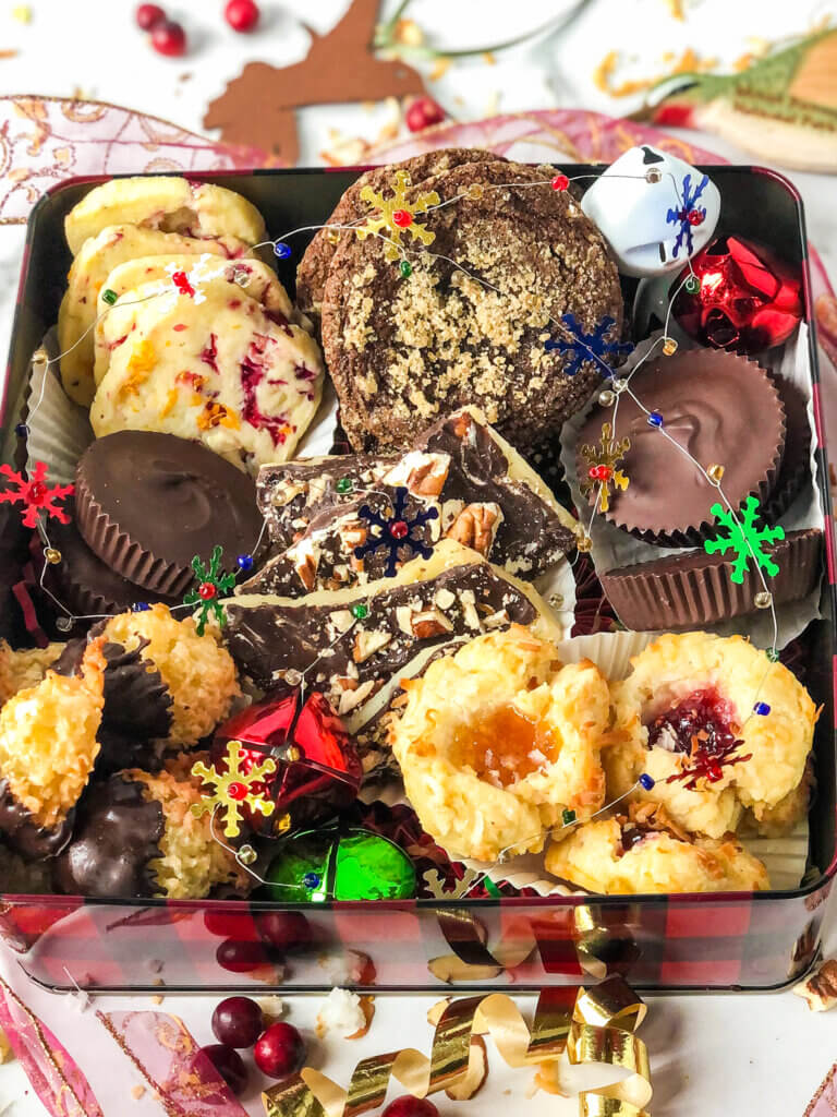 Blog post photo showing Box of Christmas cookies containing cranberry orange shortbread, molasses cookies, peanut butter cups, English toffee, chocolate-dipped macaroons, and jam thumbprints