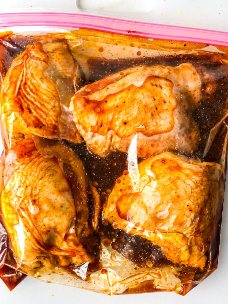 How to make Maple chicken recipe process shot: Shows 4 chicken thighs marinating in zip-top bag with smoky maple marinade