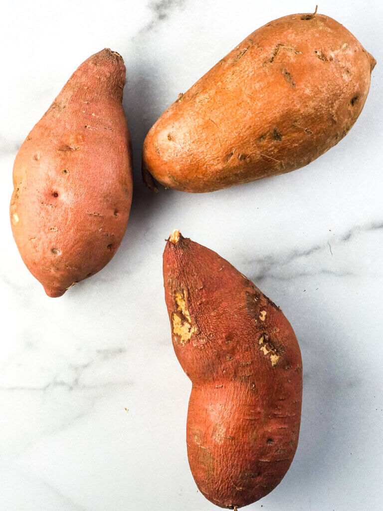 How to make Maple Sweet Potatoes with Chicken recipe process shot showing overhead view of 3 medium-sized sweet potatoes on white marble background