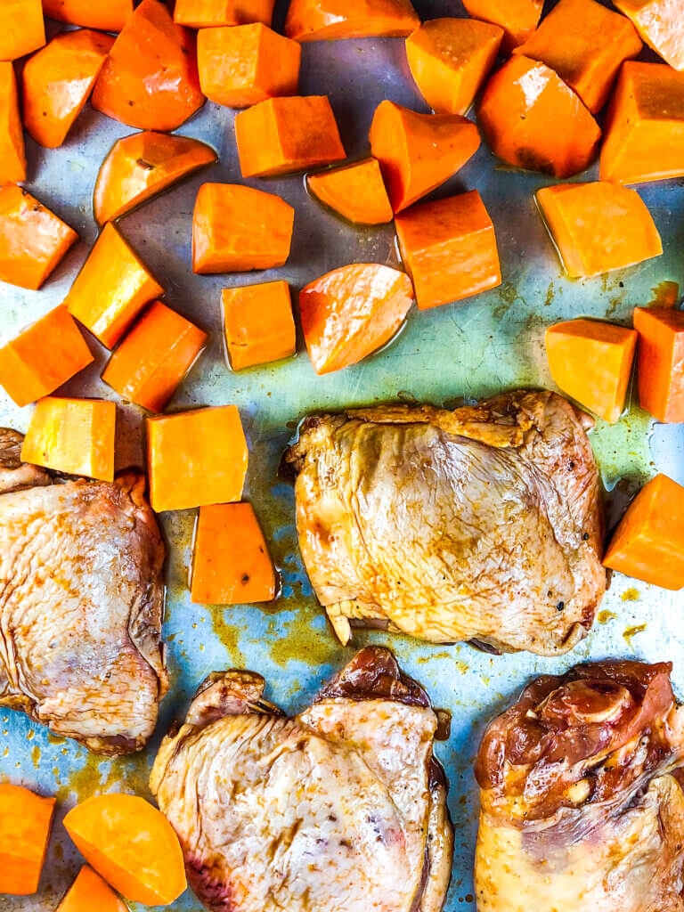 Process shot for how to make Sheet Pan chicken and sweet potatoes showing overhead vies of 4 chicken thighs and cubed sweet potatoes on either side of sheet pan