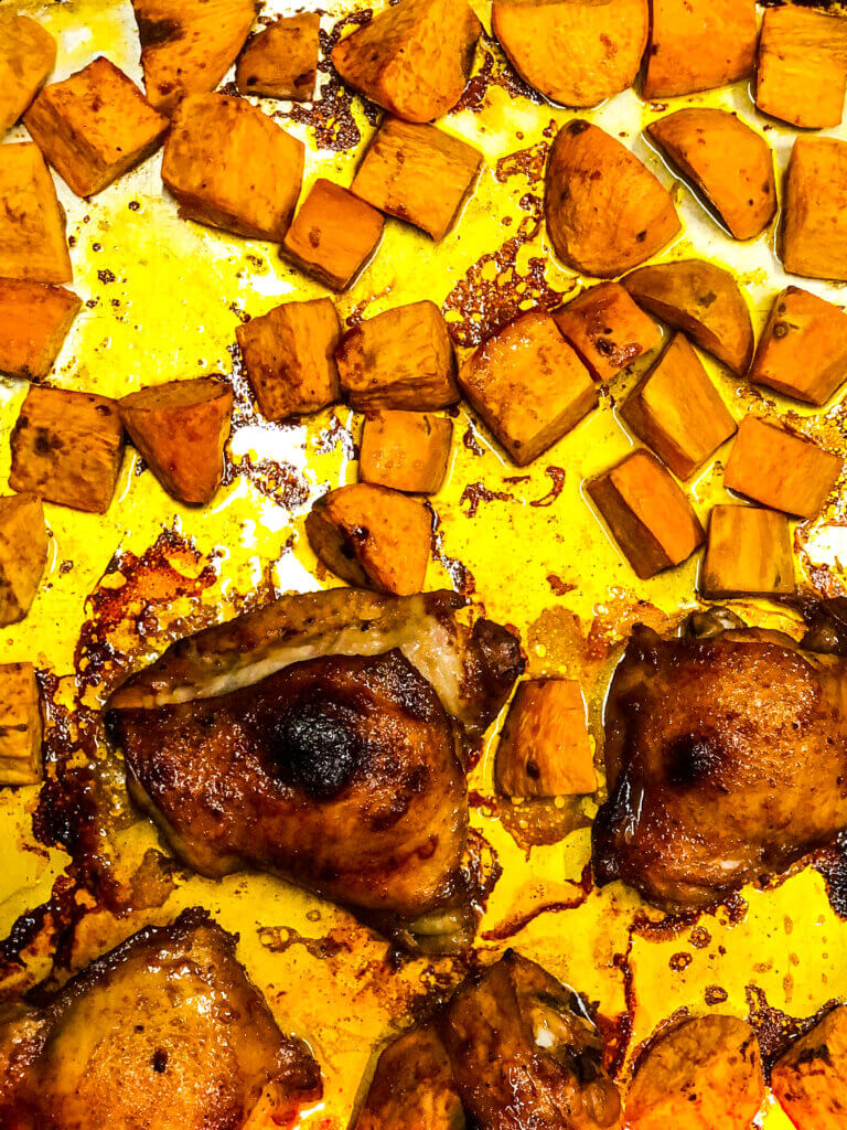 Process shot for Maple Chicken showing Overhead shot of roasted, maple-sauce coated chicken thighs and sweet potatoes