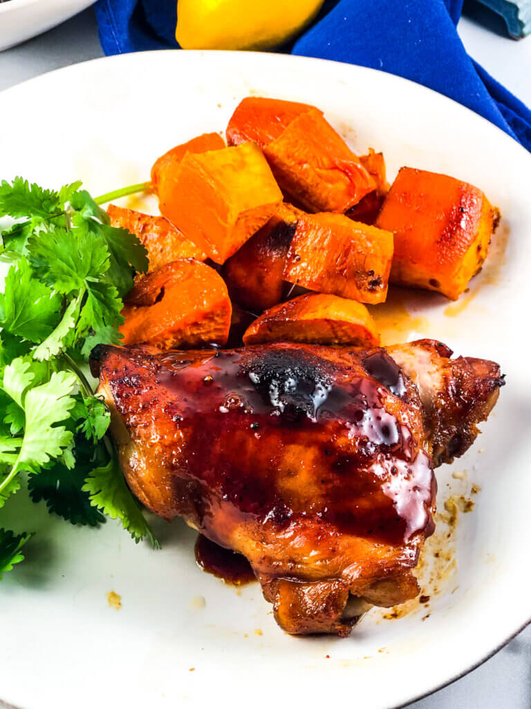 Blog photo showing overhead view of plate of roasted sheet pan maple chicken and sweet potatoes