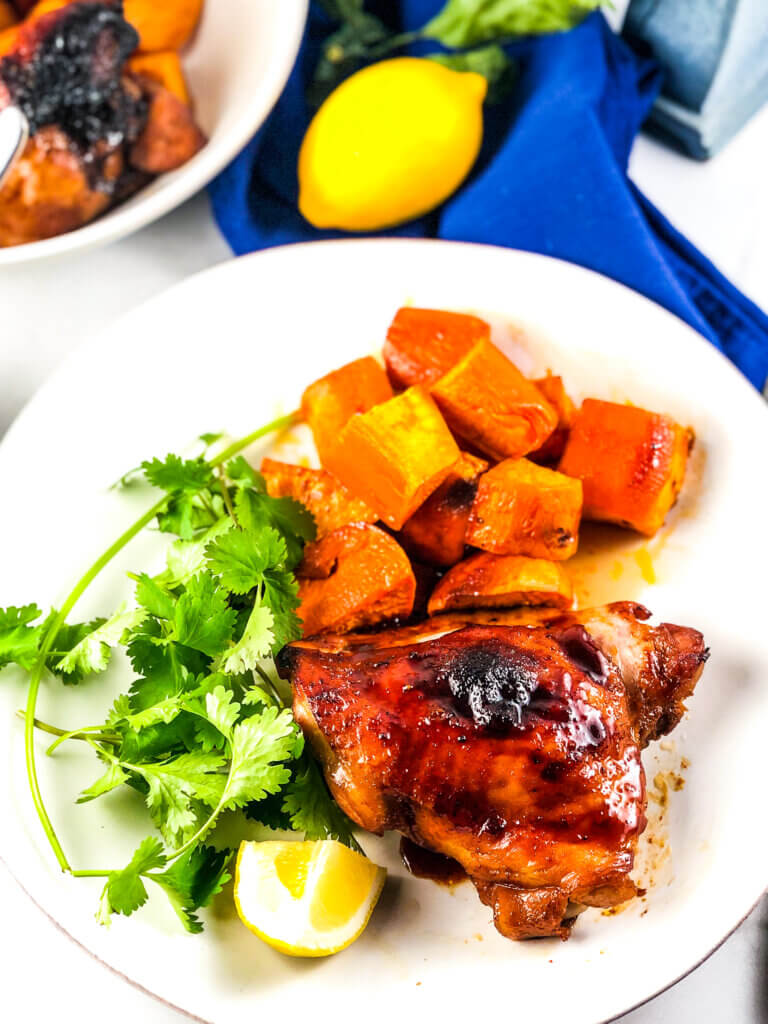 Blog photo showing overhead view of plate of roasted sheet pan maple chicken and sweet potatoes with a lemon wedge, a dish of maple sauce, a lemon and a bowl containing more chicken and sweet potatoes