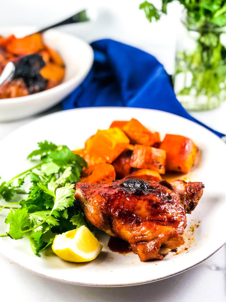 Blog photo showing plate of roasted sheet pan maple chicken and sweet potatoes with a lemon wedge. Blue napkin and vase of greens in background