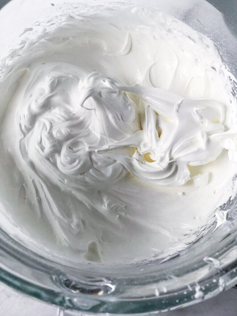 Process shot for making pavlova: Overhead view of stiff peaks in the whipped egg whites, sugar, cornstarch and lemon