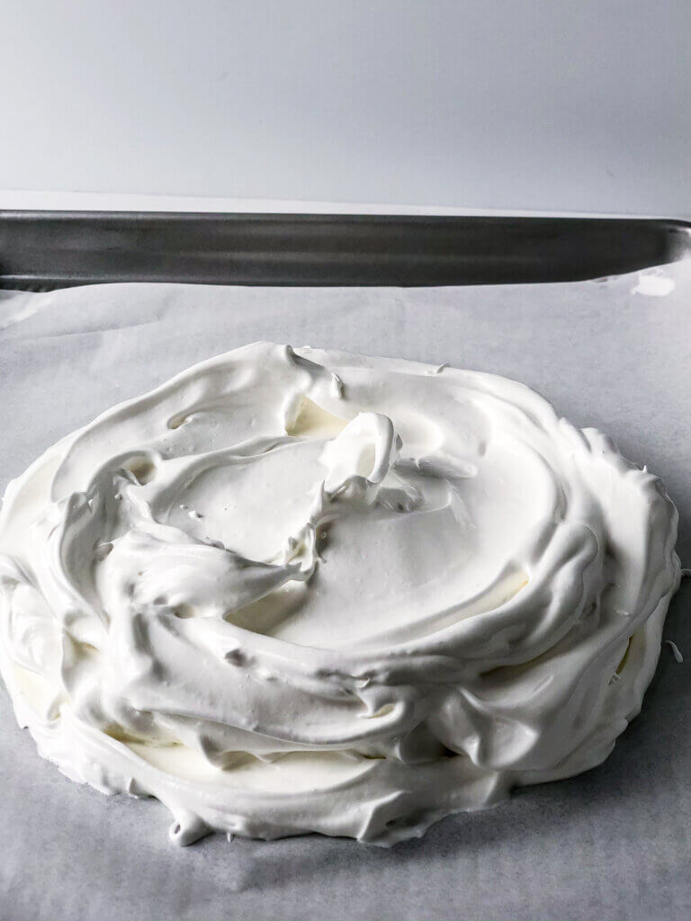 In making Pavlova, when it's ready to go int he oven, it should be slighly dome-shaped but relatively flat on top. About 2-3 inches high.