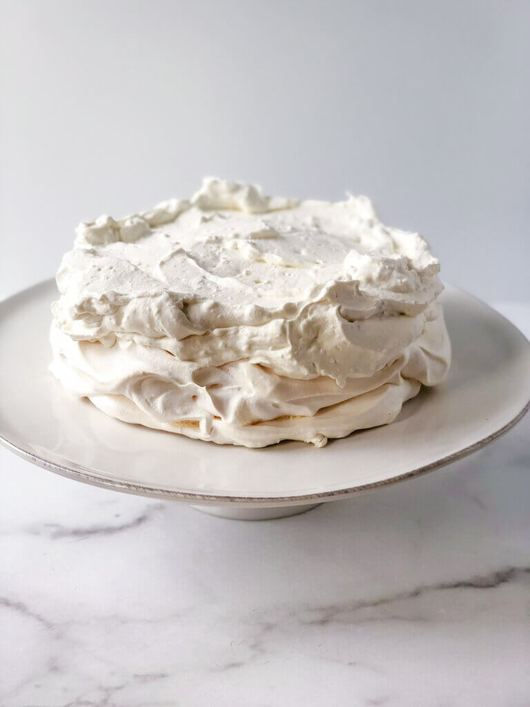 Process of making pavlova: Add a layer of whipped cream with mascarpone cheese atop the pavlova shell, leaving a flat surface for lemon curd, and/or fruit