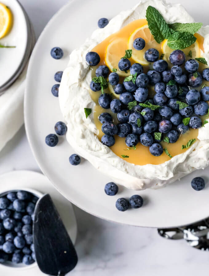 Pavlova with mascarpone cream and filled with lemon curd, sprinkled with blueberries on a white cake plate. Bowl of blueberries at bottom left.