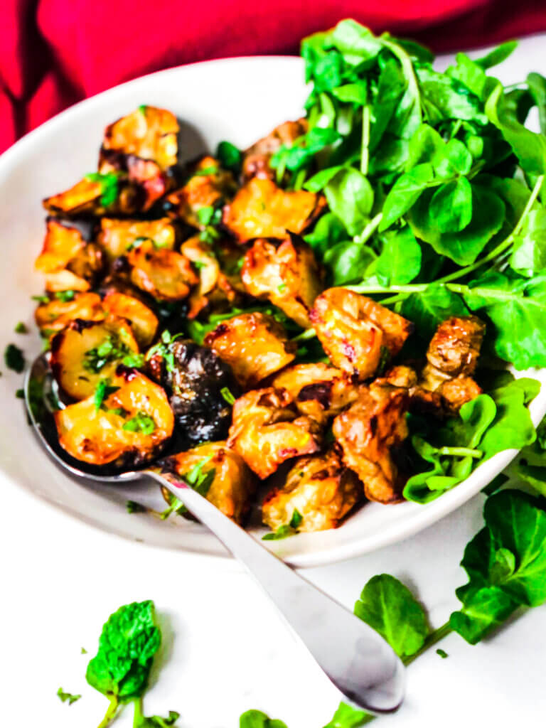 Edges of roasted Jerusalem Artichokes (sunchokes) are deep golden and crispy. Sitting over a bed of greens and sprinkled with fresh basil and mint leaves.