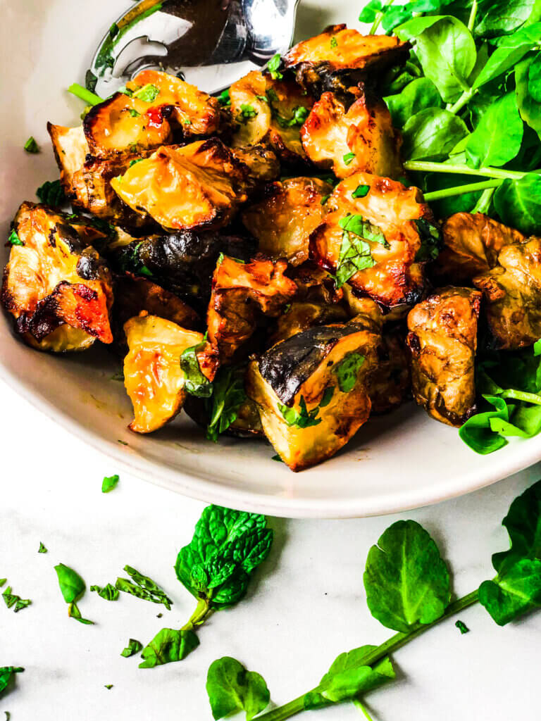 Crispy roasted Sunchokes on a bed of watercress and sprinkled with fresh basil and mint