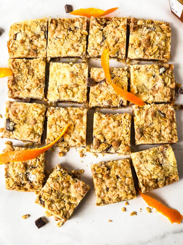 16 Oat bars in grid with several angled outward at the bottom, scattered chocolate pieces and orange rind