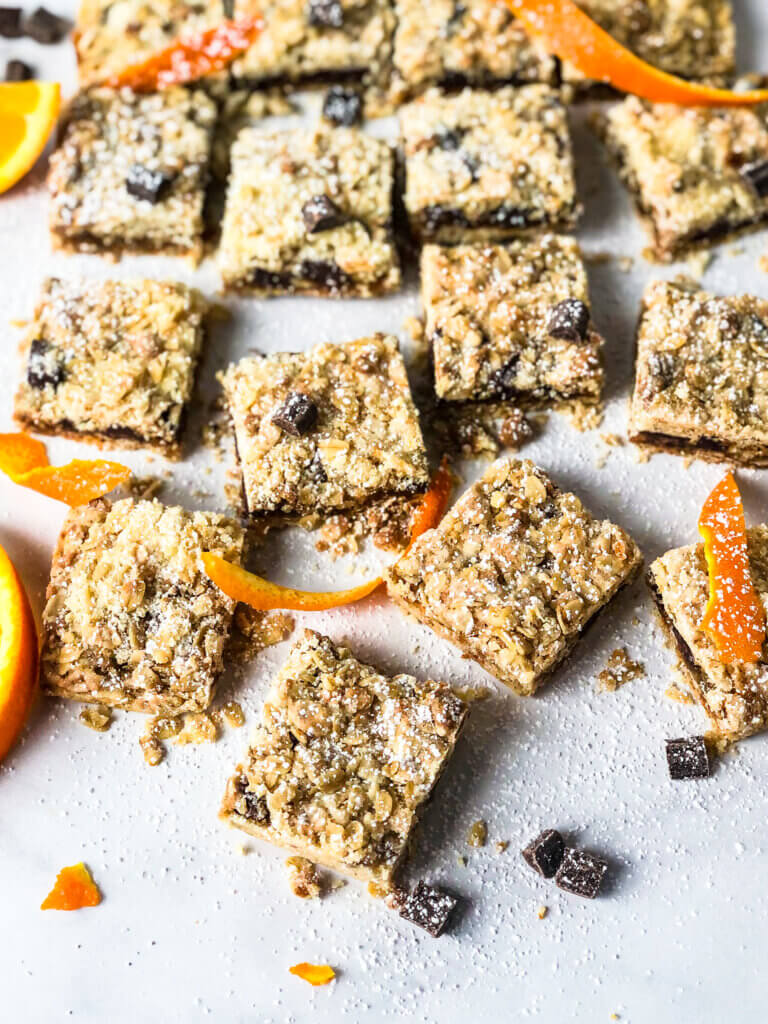 Oat Jam Bars with Chocolate scattered about with chocolate pieces and orange rind