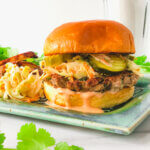 Featured Blog photo shows closeup of ginger pork burger topped with slaw, pickles and sweet and spicy dressing on bun. Sits on plate with extra slaw and crispy fries