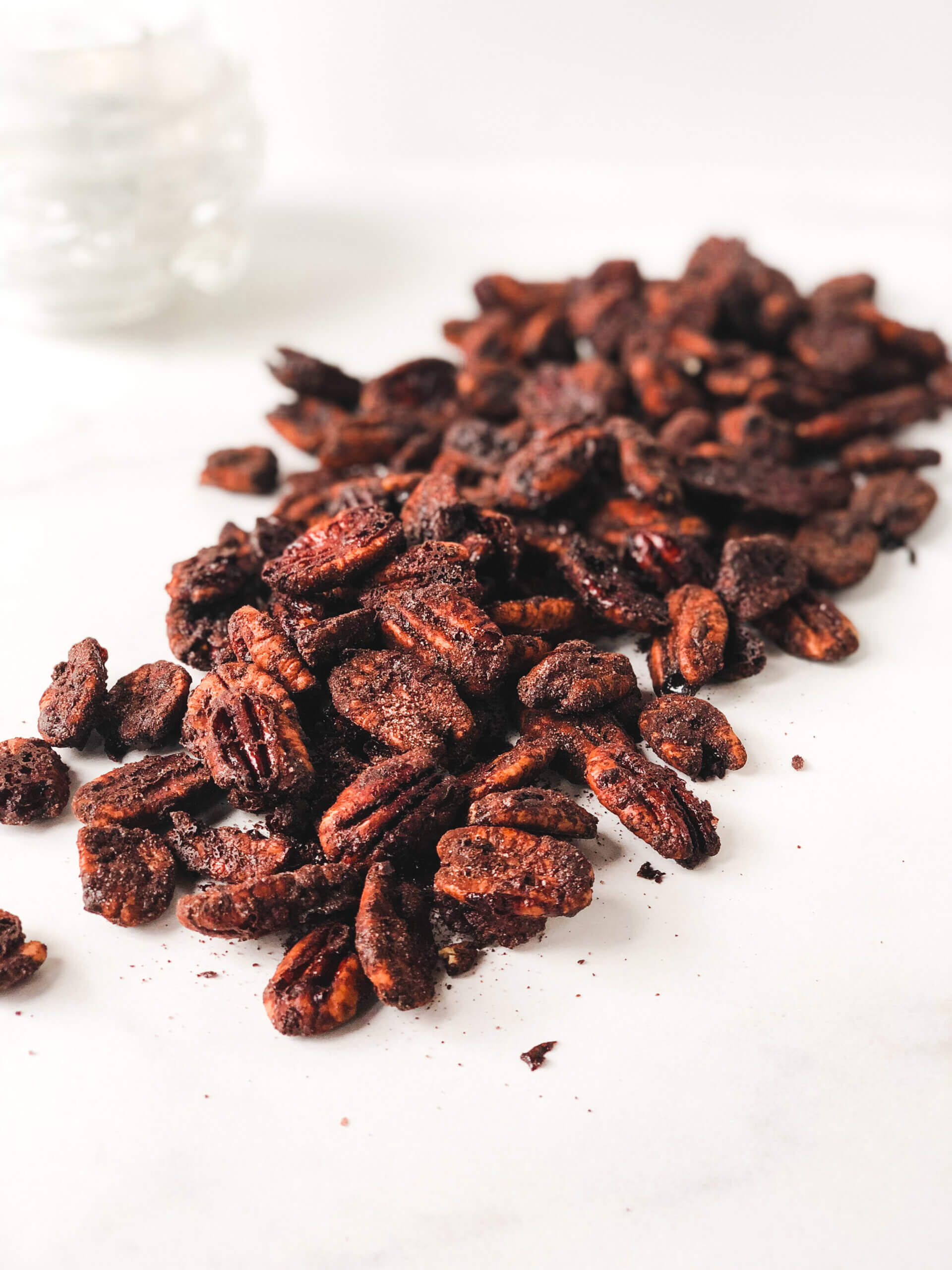 Roasted Spicy Cocoa Pecans poured over white surface in a diagonally-oriented pile. Shows how toasty and cocoa-y they are