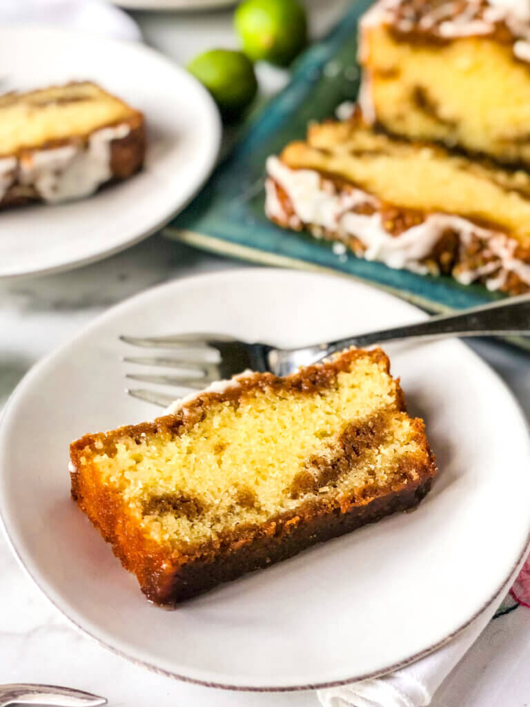 Cross section of key lime cake slice, with layers of cake and graham cracker streusel. Full loaf and another slice in background