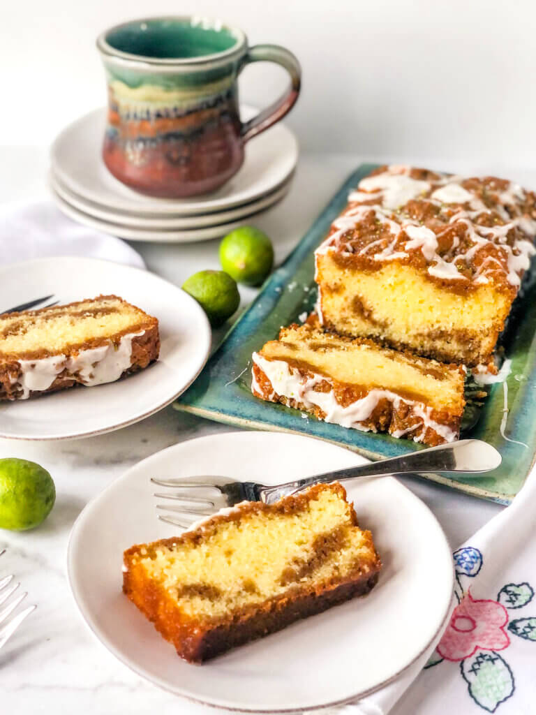Shows the graham swirl in a slice of key lime pound cake. The rest of the cake in background with a cup of coffee