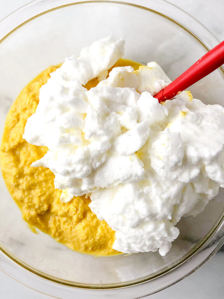 Folding of stiffened egg whites into paste made of corn, butter, egg yolks and milk