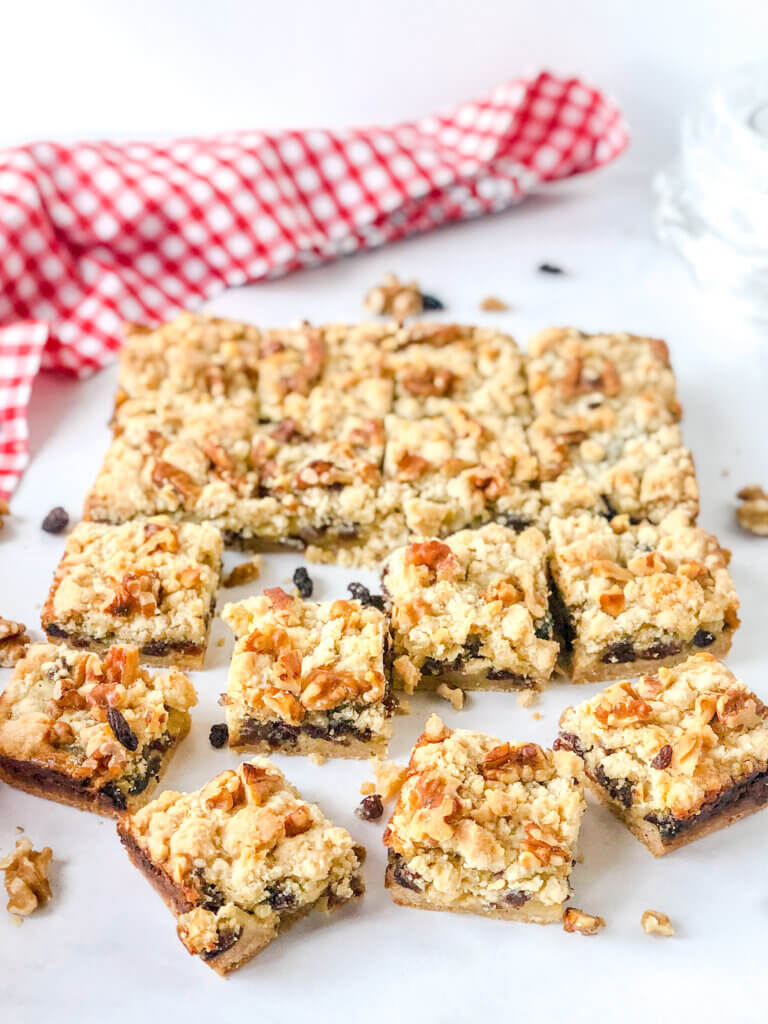 8x8 pan of sliced sour cream raisin bar cookies with layers of crust, raisin-filled custard and crumbly topping with toasted walnuts