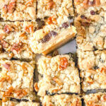 Recipe photo of sliced sour cream raisin bar cookies with layers of crust, raisin-filled custard and crumbly topping with toasted walnuts