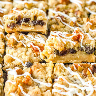 8 sliced sour cream raisin bar cookies with 2 propped up to display layers of crust, raisin-filled custard and crumbly topping with toasted walnuts
