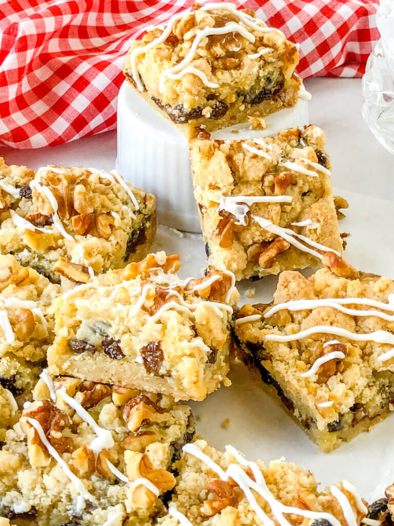 Sour cream raisin bars with layers of crisp shortbread like crust, sour cream raisin custard filling and crumb topping with toasted walnuts