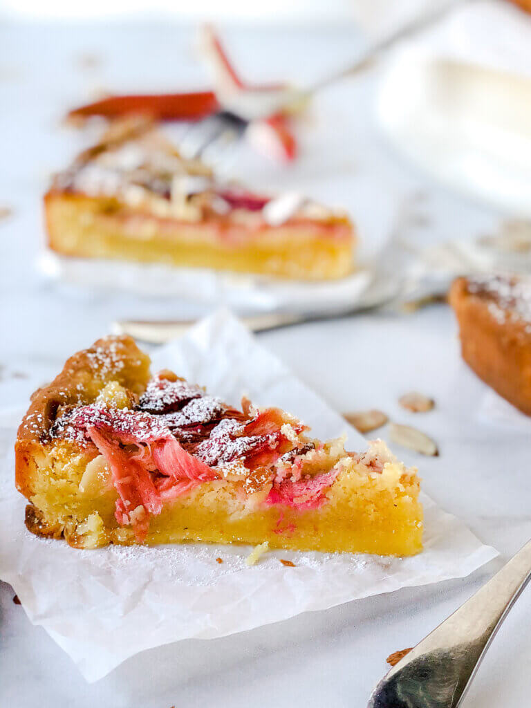 Closeup of rhubarb frangipane tart showing strips of pink rhubarb and almond filling all tucked into shortbread crust