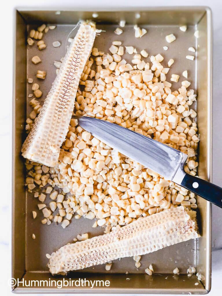 Process shot showing how to cut corn kernels
